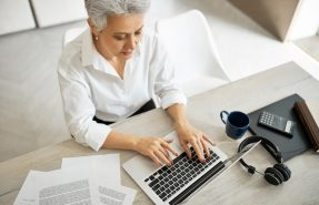 Overhead top view of successful experienced mature female translator or copywriter in formal clothing sitting at office desk with mug, papers, headphones and laptop, typing text, having serious look